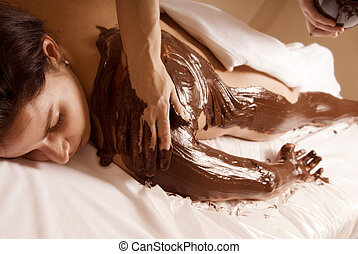 Cacao therapy - woman getting a chocolate rub at a local spa