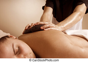 Lastone treatement - woman in a day spa getting a stone...
