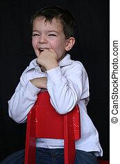 Cute Boy - a cute boy sitting backwards on an orange chair...