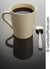 Coffee cup on black background with spoon