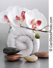 Spa - White rolled up towel with massage stones and an...