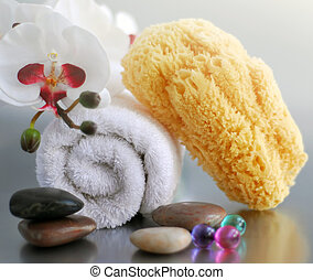 Spa - White rolled up towel with massage stones, orchid and...