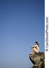 inspiration 2 - A young woman sitting on a rocky outcrop in...