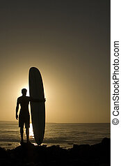 Longoard at sunset 3 - A longboarder watching he waves at...