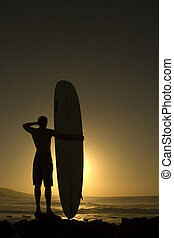Longoard at sunset 2 - A longboarder watching he waves at...