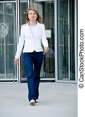 business girl - Young woman walking in front of business...