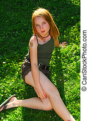 Girl grass - Young pretty girl sitting on green grass...