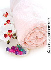 Spa - Pink rolled up towel with bath beads on white...