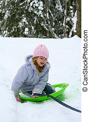 Sledding in the Snow - Little girl outdoors sledding in snow