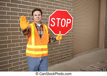 Crossing Guard at School - A school crossing guard holding a...