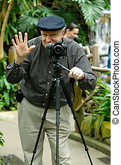 Photographer taking pictures using a tripod.