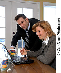 On the laptop - man and woman in business clothes with a...