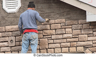 Stone Mason 1 - Stone mason putting stone on new...