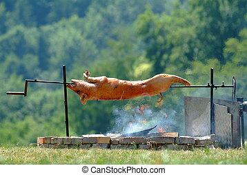 suckling pig - picture of a suckling pig on spit outside