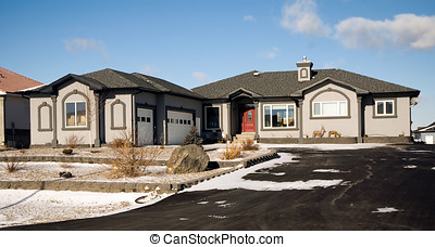 Dream home - A grey stucco luxury home with a double garage.