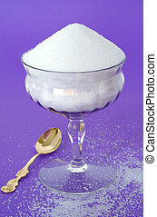 Pure White Granulated Sugar in a Vintage Glass on a Purple...