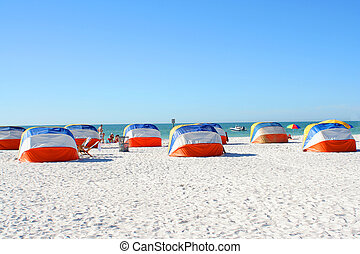 beach shelters - people relaxing on beach in shaded area in...