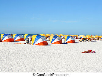beach shelters - people relaxing on beach chairs under...