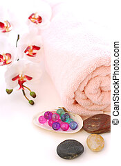 Spa - Pink rolled up towel with massage stones and bath...