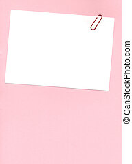 postit with paperclip - paperclip on a postit note over a...