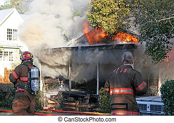 House Fire 2 - Two fireman working a flaming smoking house...