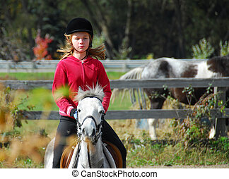 Riding - Young girl riding a white pony at countryside