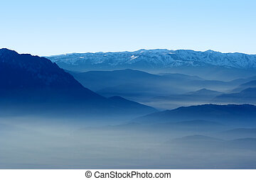 Mountains and valley in the fog - View of a valley and blue...