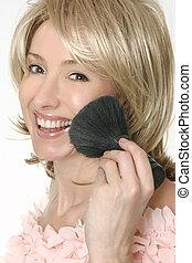 Female holding a large powder brush