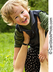 Happy child on hands of careful mum plays and laughs at a...