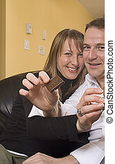 couple on couch pointing out chocolate