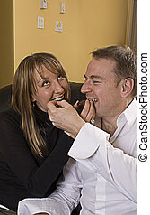 couple on couch eating chocolate