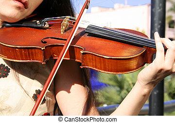 Violin - a musician performing with a violin on the balcony