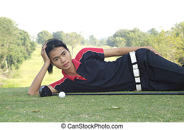 Female golf player resting - Young, female, Asian golf...