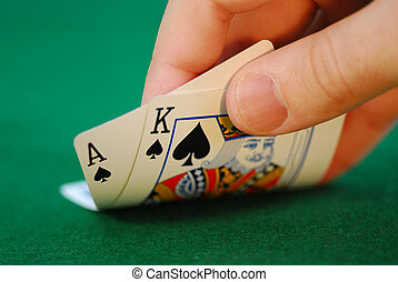 Gambling - Man\\\'s hand lifting up playing cards at a poker...