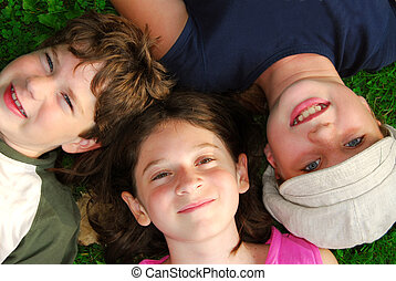 Kids - Portrait of three young children lying on grass...