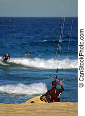 Kite-surfing - Kite surfer going into water, blurred surfers...