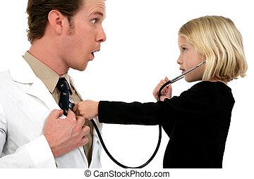 Doctor And Patient - Small girl using stethoscope on doctor