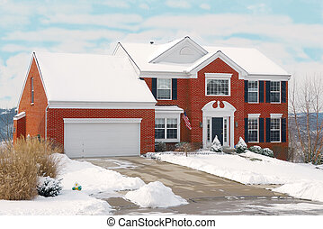 House on a Hill in Winter - a suburban brick two story home...