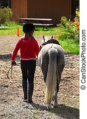 Girl and pony - Young girl leading her pony back to the...