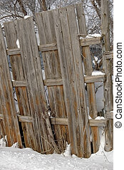 Leaning Fence - Fence surrounding junkyard in winter
