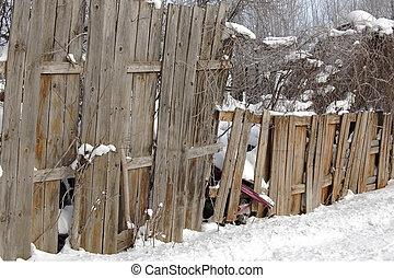 Sagging fence - Fence surrounding junkyard in winter