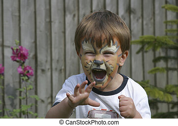 Tiger face - A young boy with tiger face painting roaring.