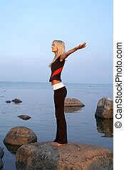 seashore meditation - picture of fit girl meditating at the...