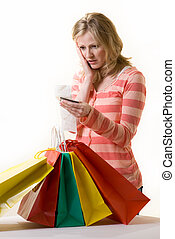 Overspending - Attractive blond woman standing in front of a...