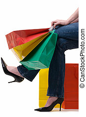 shopping - Legs of a woman holding onto a bunch of colorful...