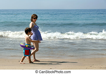 Family on the beach - Pregnant mother and her son walking on...