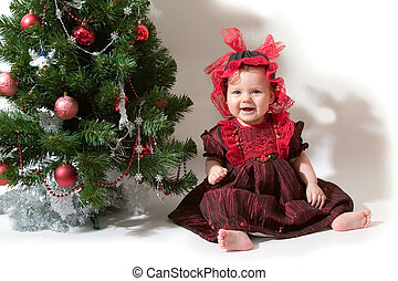christmas tree and baby-girl - baby girl sitting next to the...