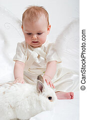 fairy plays with white rabbit - cute little girl dressed...