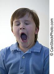 Boy yawning - A tired young boy having a big yawn