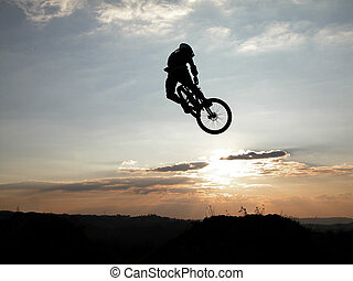 Mountain bike jump at the sunset